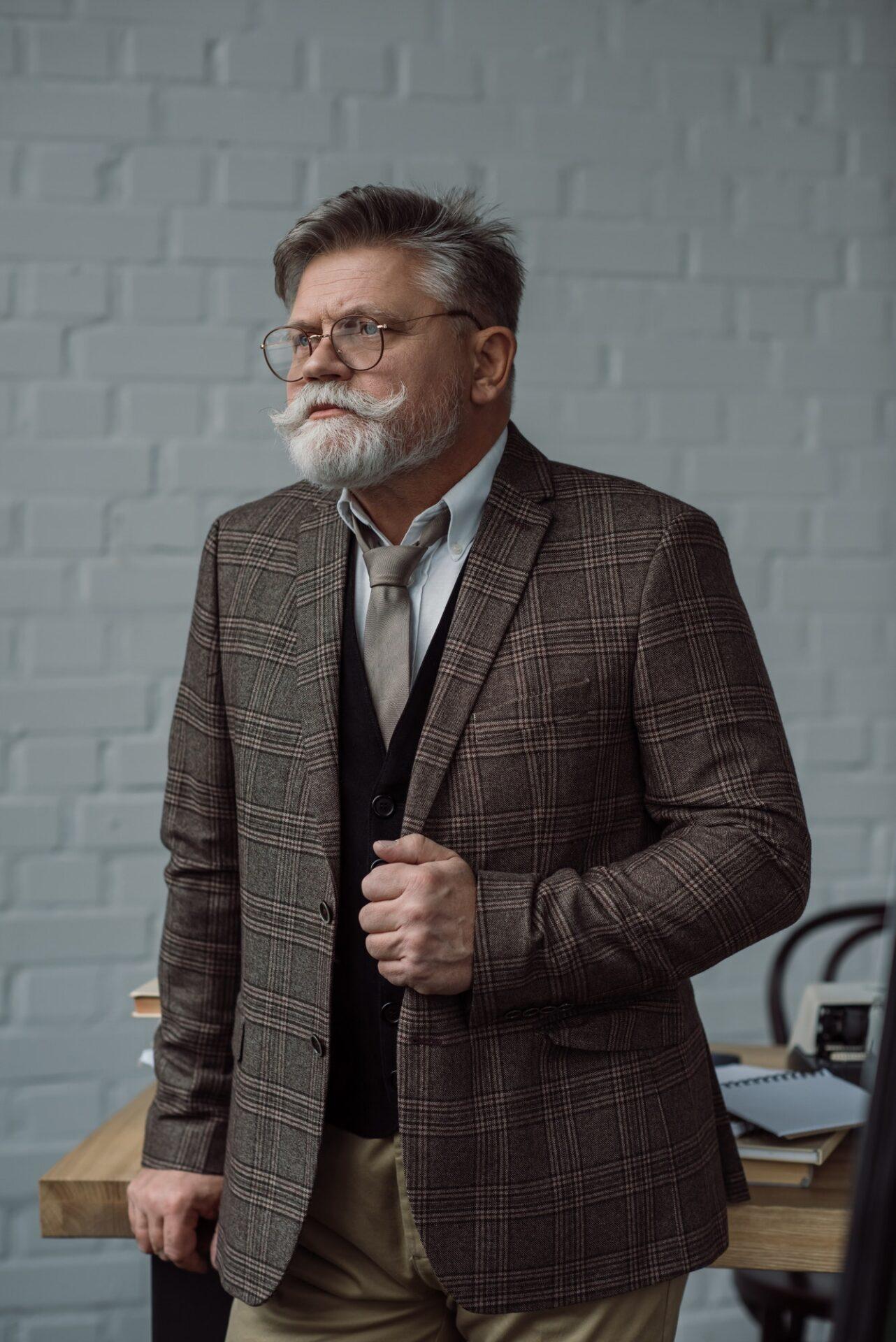senior-writer-in-tweed-suit-and-eyeglasses-near-workplace.jpg